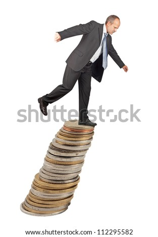 Unbalanced business man on a top of coins pile -concept of business uncertainty