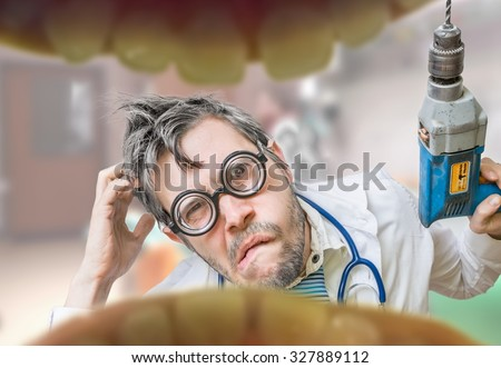 Uncertain and unsure crazy dentist doctor looks into mouth and wants to drill tooth decay. - stock photo