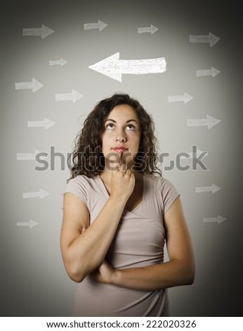 Uncertain girl is looking at arrows. Girl full of doubts and hesitation. Young woman doing something. - stock photo