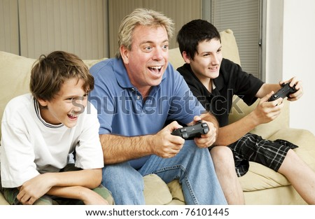 Uncle plays video games with his nephews.  Could also be father. - stock photo