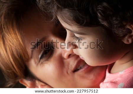 Unconditional mother love while staring at her daughter can be seen in her eyes. - stock photo