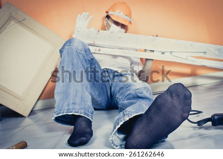 unconscious asian workman lying on the floor , focus at left foot / orange wall background + art filter - stock photo