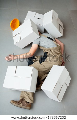 Unconscious handyman lying crushed by heavy cartons  - stock photo