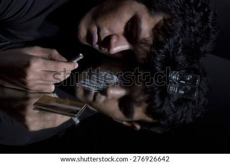 Unconscious man with drugs and rolled up banknote - stock photo