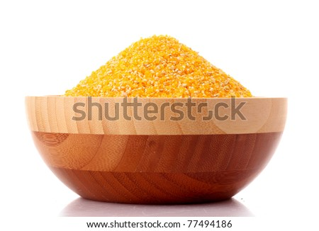 Uncoocked hominy grits  in bowl isolated on white - stock photo