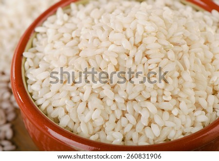 Uncooked arborio rice in a bowl. Selective focus - stock photo