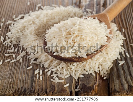 Uncooked basmati rice in a wooden  spoon . Selective focus - stock photo