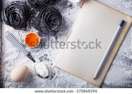 Uncooked black pasta and ingredients for homemade spaghetti Italian food.Notepad to write the prescription.Copy space.selective focus - stock photo