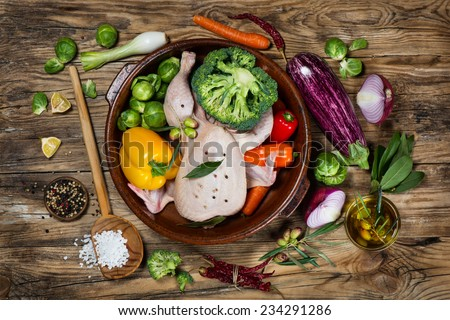 uncooked chicken with vegetables and spices in a pan on a old rustic wooden table, view from above - stock photo