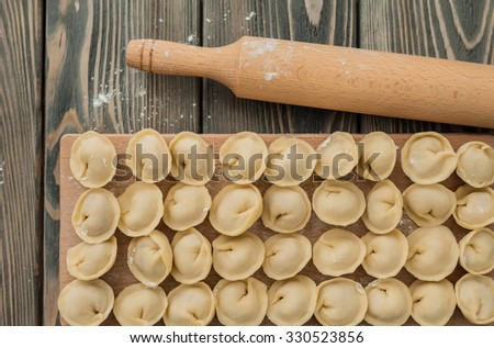 Uncooked dumplings with meat on the wooden desk. - stock photo