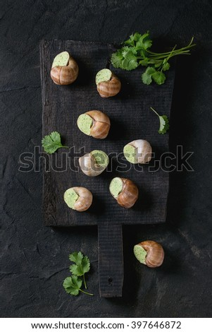 Uncooked Escargots de Bourgogne - Snails with herbs butter, gourmet dish, on black wooden chopping board with parsley over black textured background. Top view. - stock photo