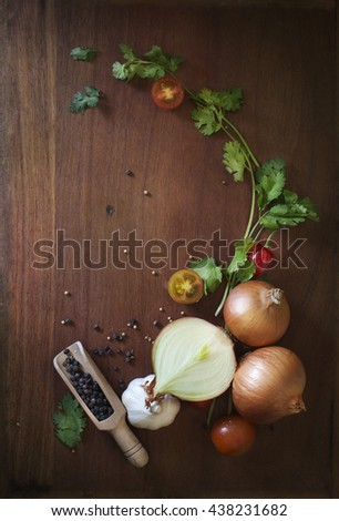 Uncooked fresh vegetables, yellow onion, garlic, cherry tomato, other herbs and spices on wooden background. Text space images.