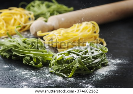 Uncooked green pasta on the black table, selective focus - stock photo