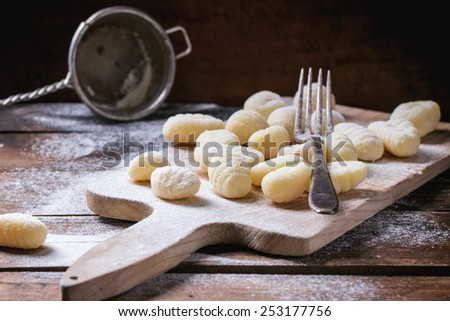 Uncooked homemade potato gnocchi with fork and strainer on vintage cutting board over wooden table with flour. See series. - stock photo
