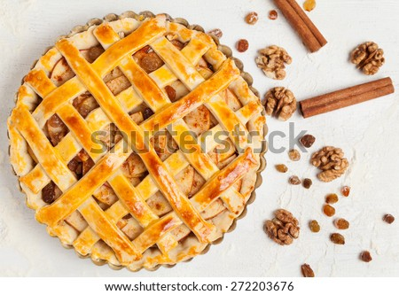 Uncooked homemade rustic apple pie preparation greased with egg yolk on white kitchen background - stock photo