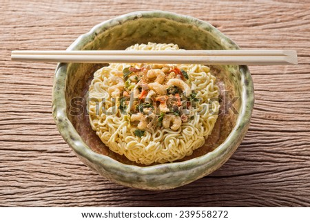 uncooked hot and sour flavor instant noodle with ingredient in ceramic bowl with bamboo chopsticks - stock photo
