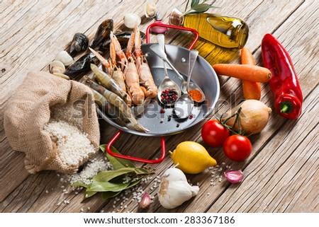 Uncooked ingredients of spanish seafood paella on a rustic wooden background - stock photo
