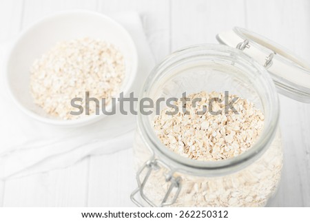 uncooked instant oatmeal in glass jar on white background - stock photo