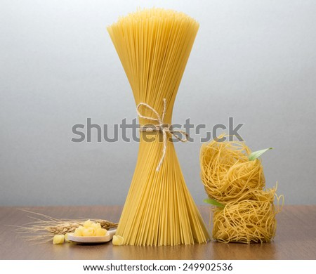Uncooked italian pasta on table - stock photo