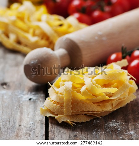 Uncooked italian pasta on the table, selective focus and square image - stock photo