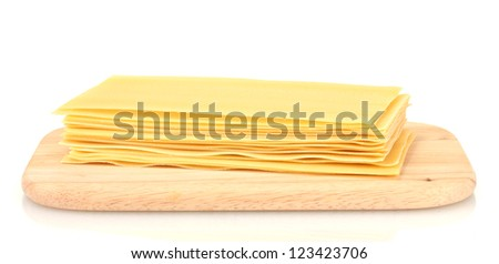 Uncooked lasagna pasta on cutting board isolated on white