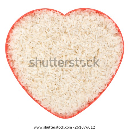 Uncooked parboiled rice in a red heart plate isolated on white background - stock photo