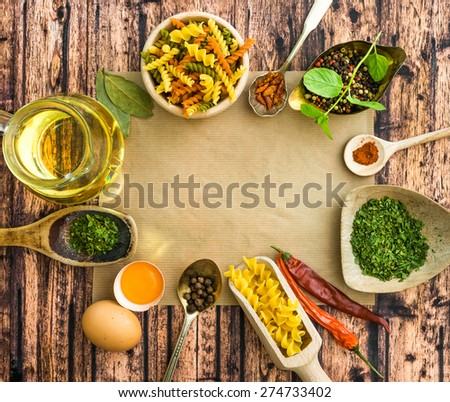 uncooked pasta and spices on a dark wooden background - stock photo