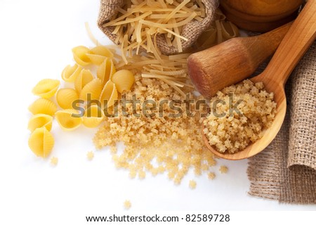 Uncooked pasta in the wooden spoon on the white background - stock photo