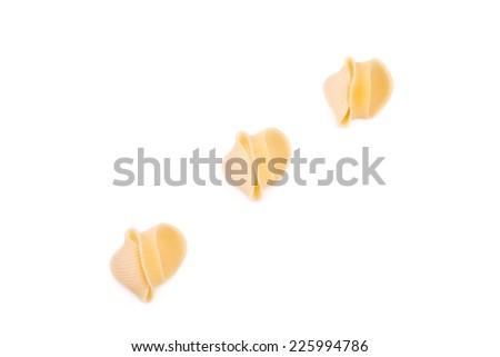 Uncooked pasta lumaconi. Isolated on a white background. - stock photo