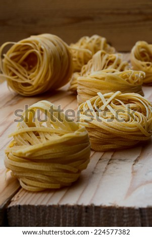 uncooked pasta on wood background, selective focus - stock photo