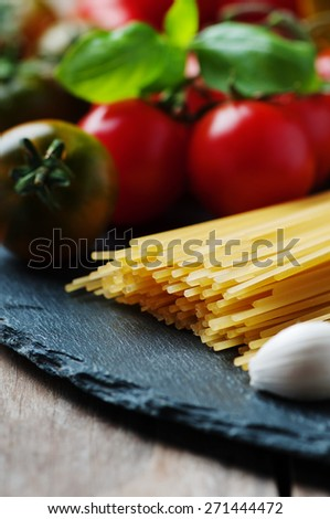 Uncooked pasta with tomato, basil and oil, selective focus - stock photo