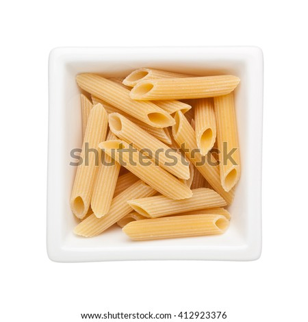 Uncooked penne rigate in a square bowl isolated on white background