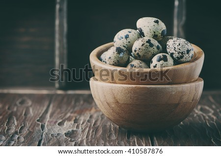 Uncooked quail eggs on the wooden table, selective focus and toned image - stock photo