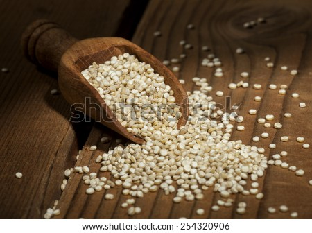Uncooked quinoa in the wooden spoon on a wooden background. - stock photo