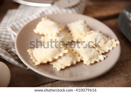 Uncooked ravioli on plate on wooden table - stock photo