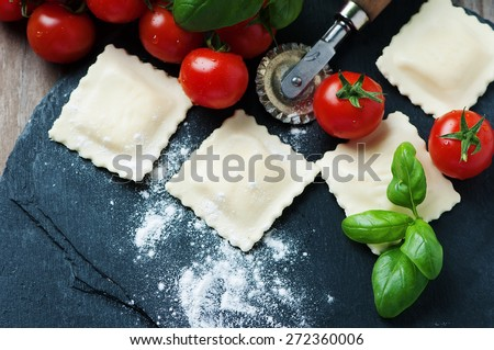 Uncooked ravioli with tomato and basil, selective focus - stock photo