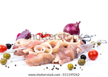 uncooked raw piece of chicken on skewers with serving spices on white background - stock photo
