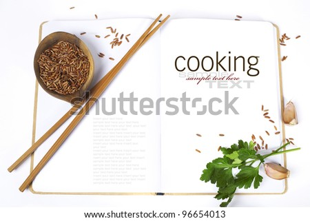 uncooked rice,  chopsticks, garlic, parsley and opened notebook (with easy removable sample text) - stock photo
