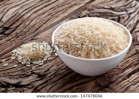 Uncooked rice in a bowl on a dark wooden table. - stock photo