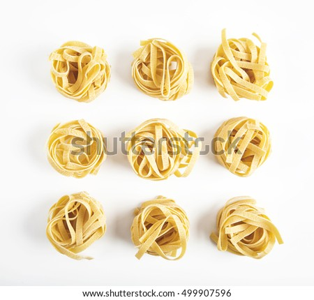 Uncooked rolled traditional italian pasta on white background, isolated. Portion of raw fettuccine or tagliatelle or pappardelle. Dry pasta from whole wheat flour. Ingredients for tasty dish