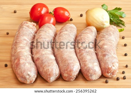 Uncooked sausage with vegetables on the chopping board