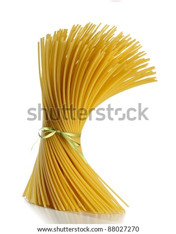 uncooked spaghetti tied with green ribbon running on white background - stock photo