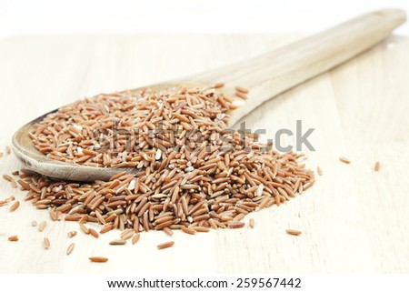 Uncooked Thai brown rice in ladle , rice Healthy Food - stock photo