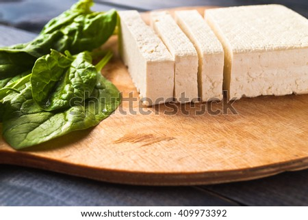 Uncooked tofu slices and green leaves of fresh spinach on cutting board - stock photo