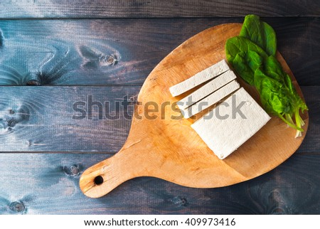 Uncooked tofu slices and green leaves of fresh spinach on cutting board and rustic wooden background - stock photo