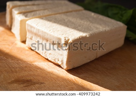 Uncooked tofu slices and green leaves of fresh spinach on cutting board. Close up - stock photo