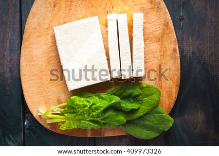 Uncooked tofu slices and green leaves of fresh spinach on cutting board. Top view - stock photo