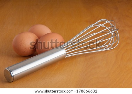 Uncracked eggs and a silver whisk all on a cutting board. - stock photo