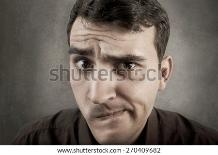 Undecided young student man isolated over grey background.Doubt facial expression close-up of a young man.
