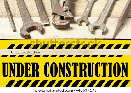Under construction board with repair tools. Wrench on wooden background. Top view